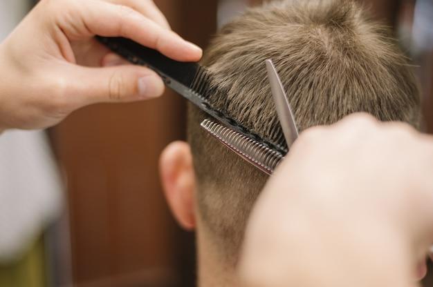 クライアントに散髪を与えるクローズアップビューのヘアスタイリスト