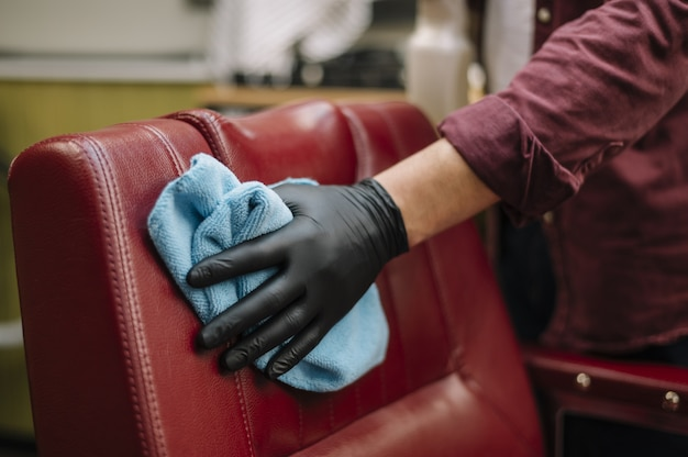 椅子を掃除するヘアスタイリストのクローズアップ