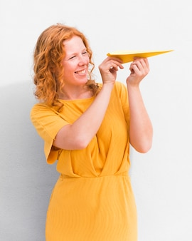 Улыбающаяся девушка держит бумажный самолетик