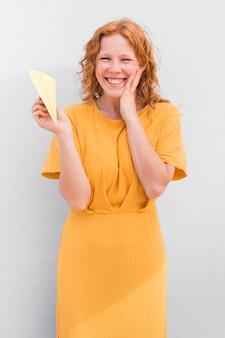 Счастливая девушка держит бумажный самолетик