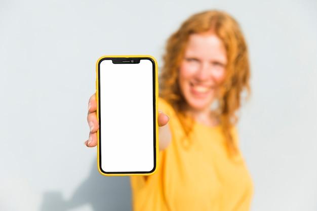 Смайлик девушка держит смартфон