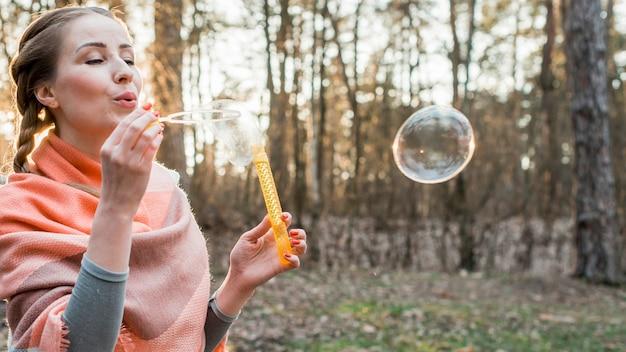 Молодая женщина делает пузыри