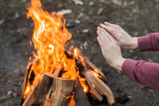 Высокий угол женщина потепления у костра
