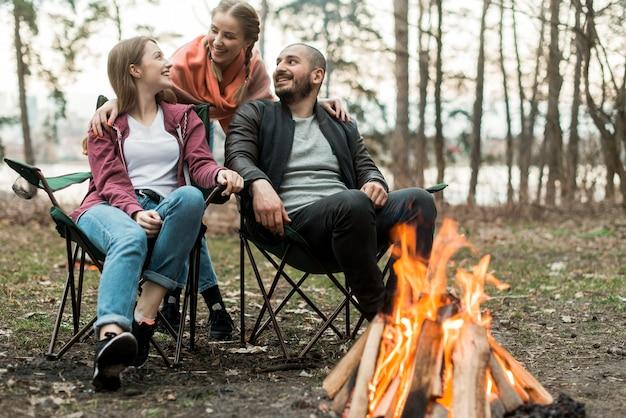たき火で座っている低角度の友達