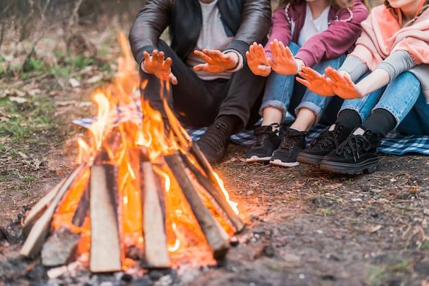 Друзья крупным планом греются в пожарном лагере