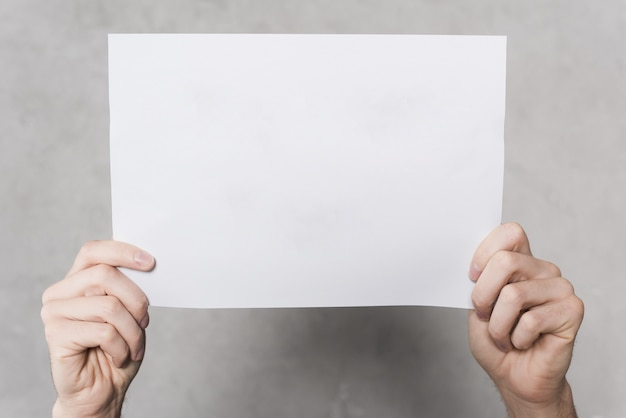 Вид спереди руки держат чистый лист бумаги