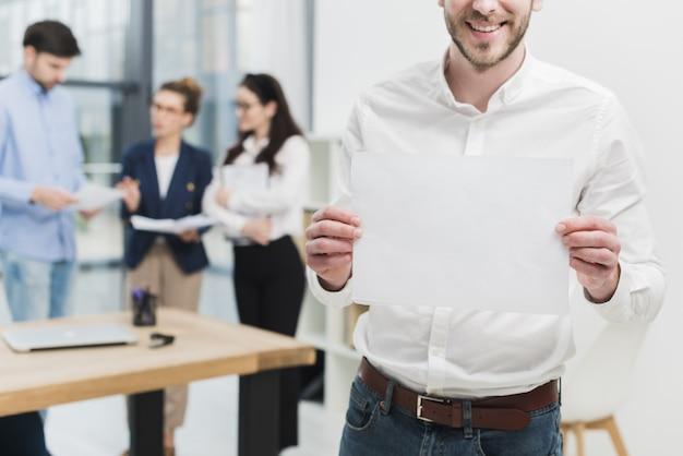 Вид спереди человека в офисе, держа чистый лист бумаги