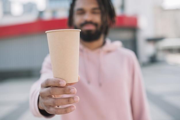 コーヒーカップを保持しているアフリカ系アメリカ人の男