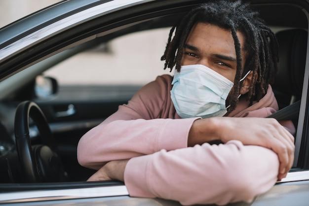 アフリカ系アメリカ人のドライバーが医療用マスクを着用