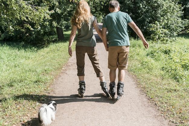 公園を歩いてローラースケート靴を着ているカップル