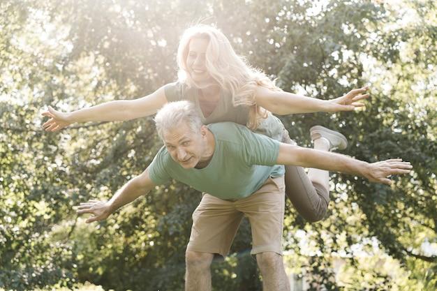 Пожилая пара дурачится в парке