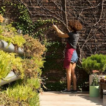 Вид сзади молодая женщина заботится о растениях