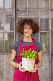 Женщина держит растение в белом горшке