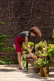 Длинный выстрел женщина заботится о своих растениях в теплице