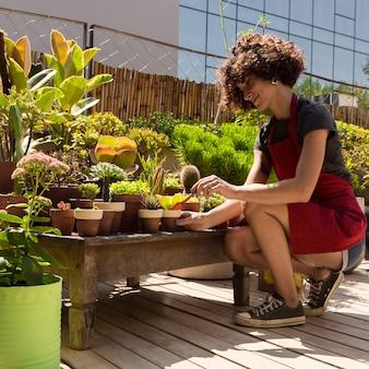 Вид сбоку женщина улыбается во время садоводства