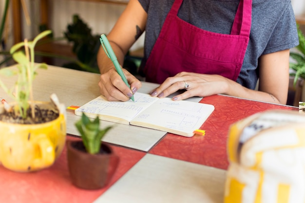彼女のノートに何かを書く庭師の正面図
