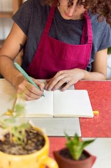 植物の横にある彼女のノートに何かを書く若い女性
