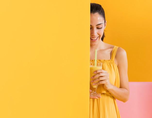 ジュースのグラスと黄色のドレスを着た女性