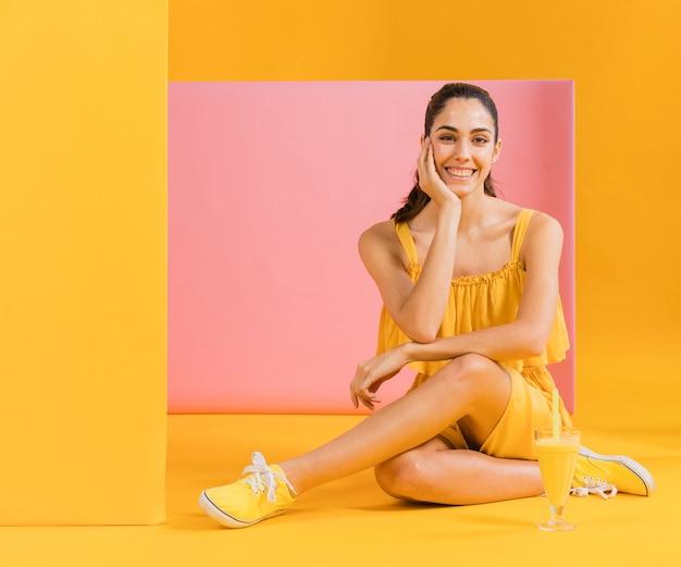 床に座って黄色のドレスを着た女性