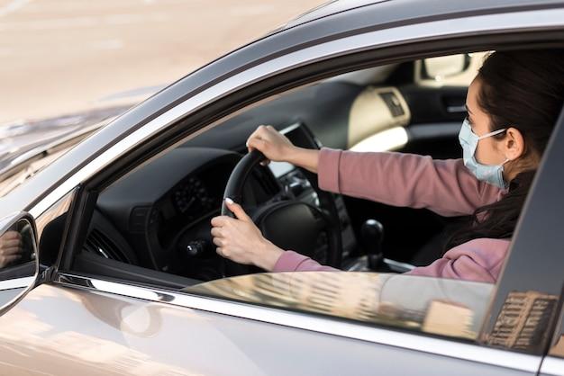 医療用マスクを着用し、運転する高い視野の女性