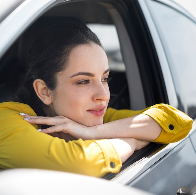 Вид сбоку женщина, опираясь на окно автомобиля