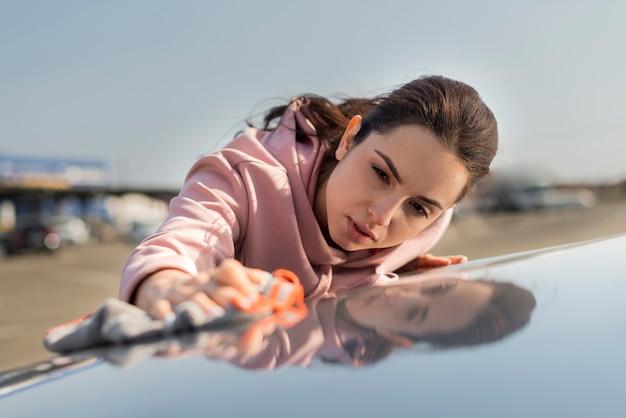 車のフロントビューのボンネットを掃除する女性