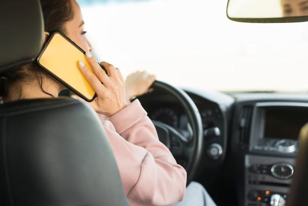 運転と電話で話している女性