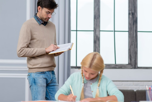 立っている正面教師と彼に耳を傾ける子供