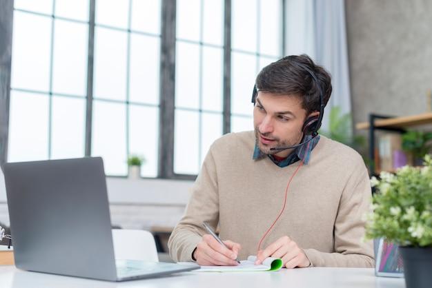 オンライン会議を持つヘッドフォンを持つ男