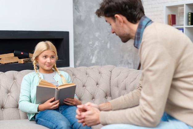 ソファーで本を読む少女