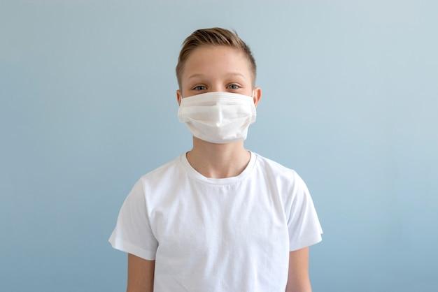 屋内で医療用マスクを着ている少年