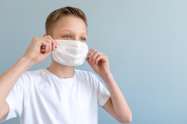 Мальчик смотрит в сторону и держит его маску