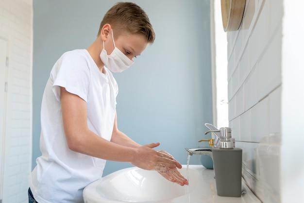 医療マスクを着用し、彼の手の側面図を洗う少年