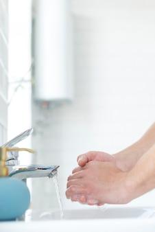 Вид сбоку мытья рук в раковине