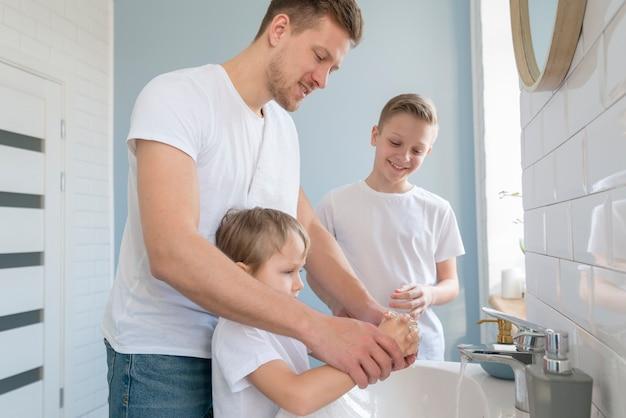 Отец с братьями и сестрами моют руки в ванной комнате