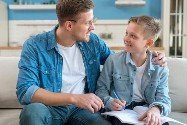 幸せな父親が息子の宿題を手伝って