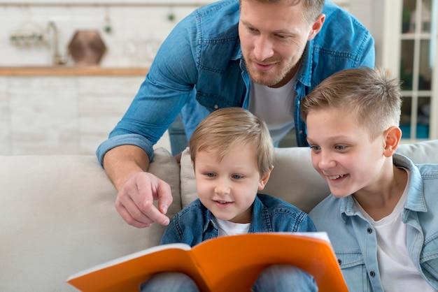 Отец с братьями и сестрами, читая вместе