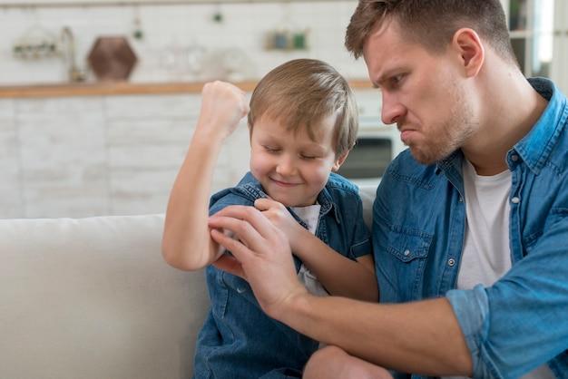 Сильный ребенок показывает мышцы своему отцу