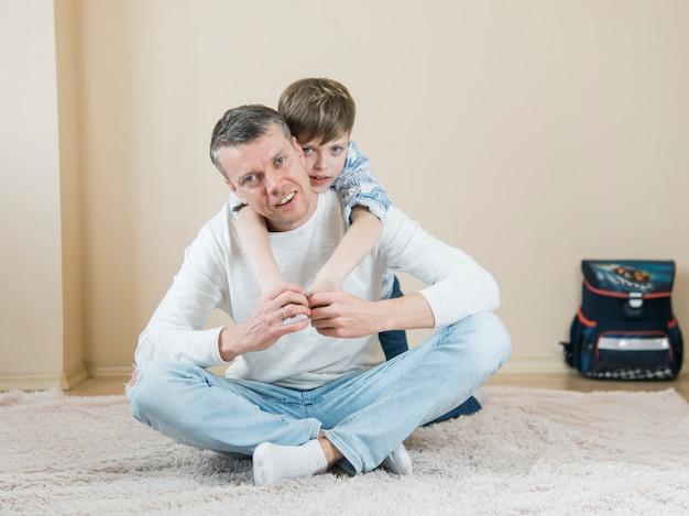 父と息子がカーペットの上で遊んで