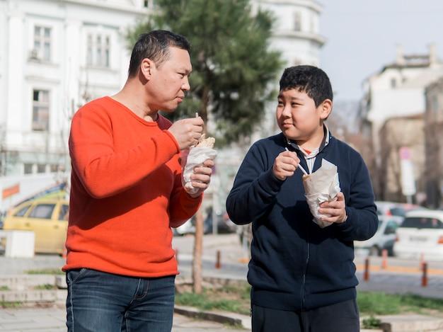 アジアの父と息子が屋外で食べる