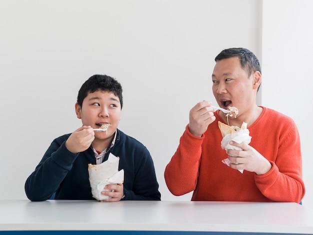アジアの父と息子のファーストフードを食べる