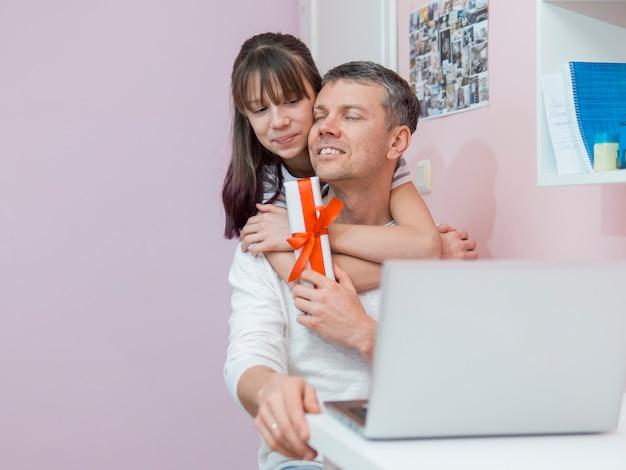 娘は父親に贈り物と抱擁を提供します