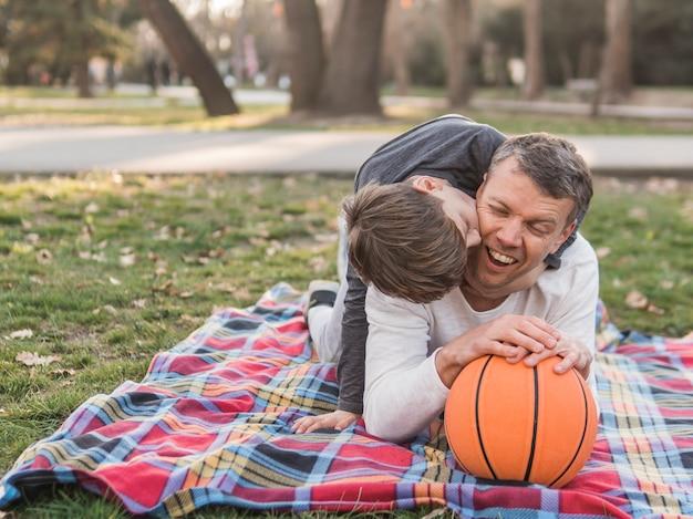 父と息子は公園でバスケットボールを