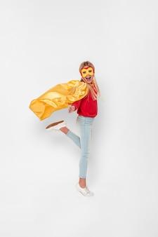 Боковой вид девушка с костюмом супергероя прыгает