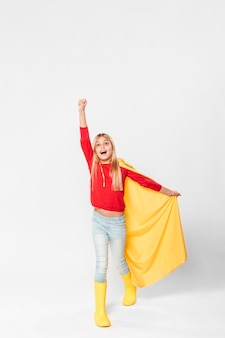 スーパーヒーローの衣装で幸せな女の子