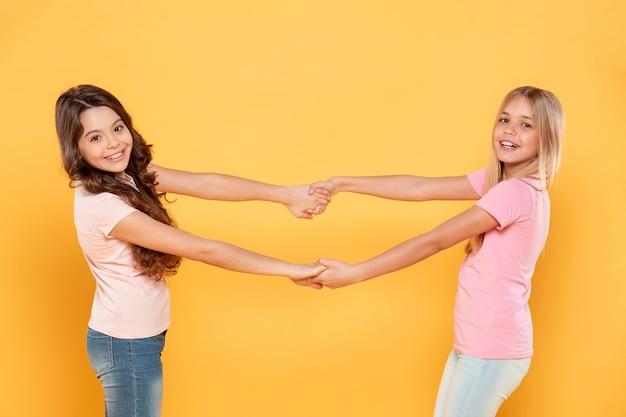 Вид сбоку девушки держатся за руки
