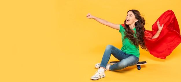 スケートボード上のヒーローの衣装の肖像画の女の子