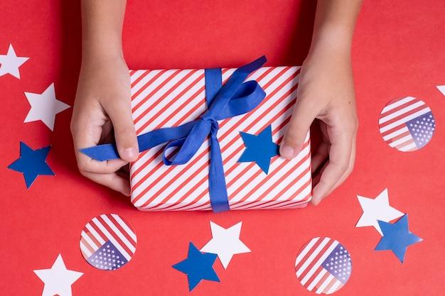 Руки взгляда сверху держа флаг сша обернутый подарок с украшением