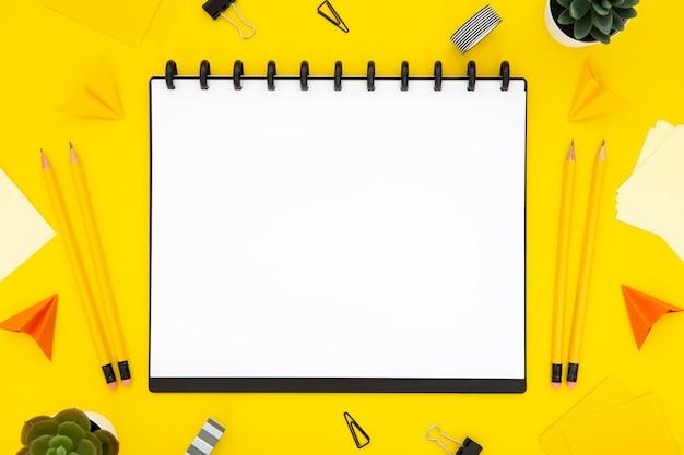 黄色の背景にフラットレイアウト文房具配置