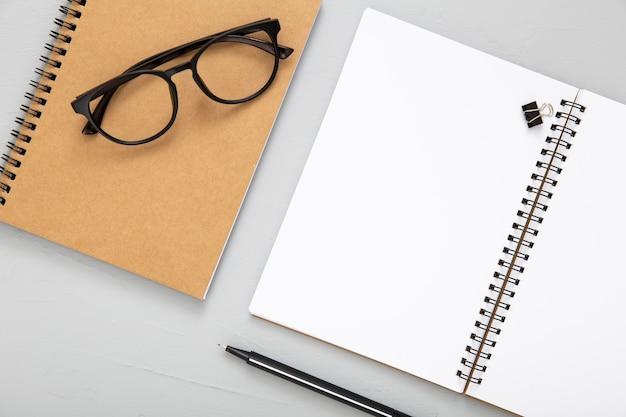 Ассортимент элементов стола с открытой пустой записной книжкой